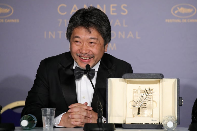 Hirokazu Kore-Eda sits at a press conference table, smiling, with his Palme d'Or.
