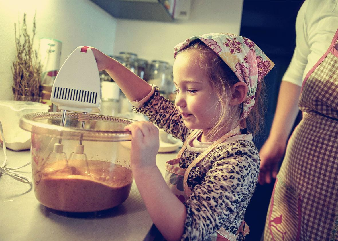 Little girl mixing dough for a birthday cake.