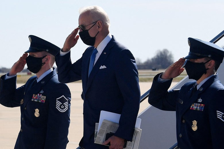 Biden salutes as he disembarks from Air Dorce One, two officers around him saluting, too.