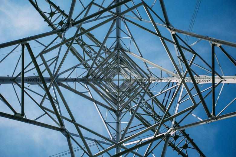 A low-angle view of a transmission tower.