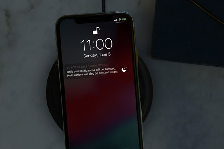 An iPhone with a dimmed display, using Apple's new Do Not Disturb during bedtime feature.