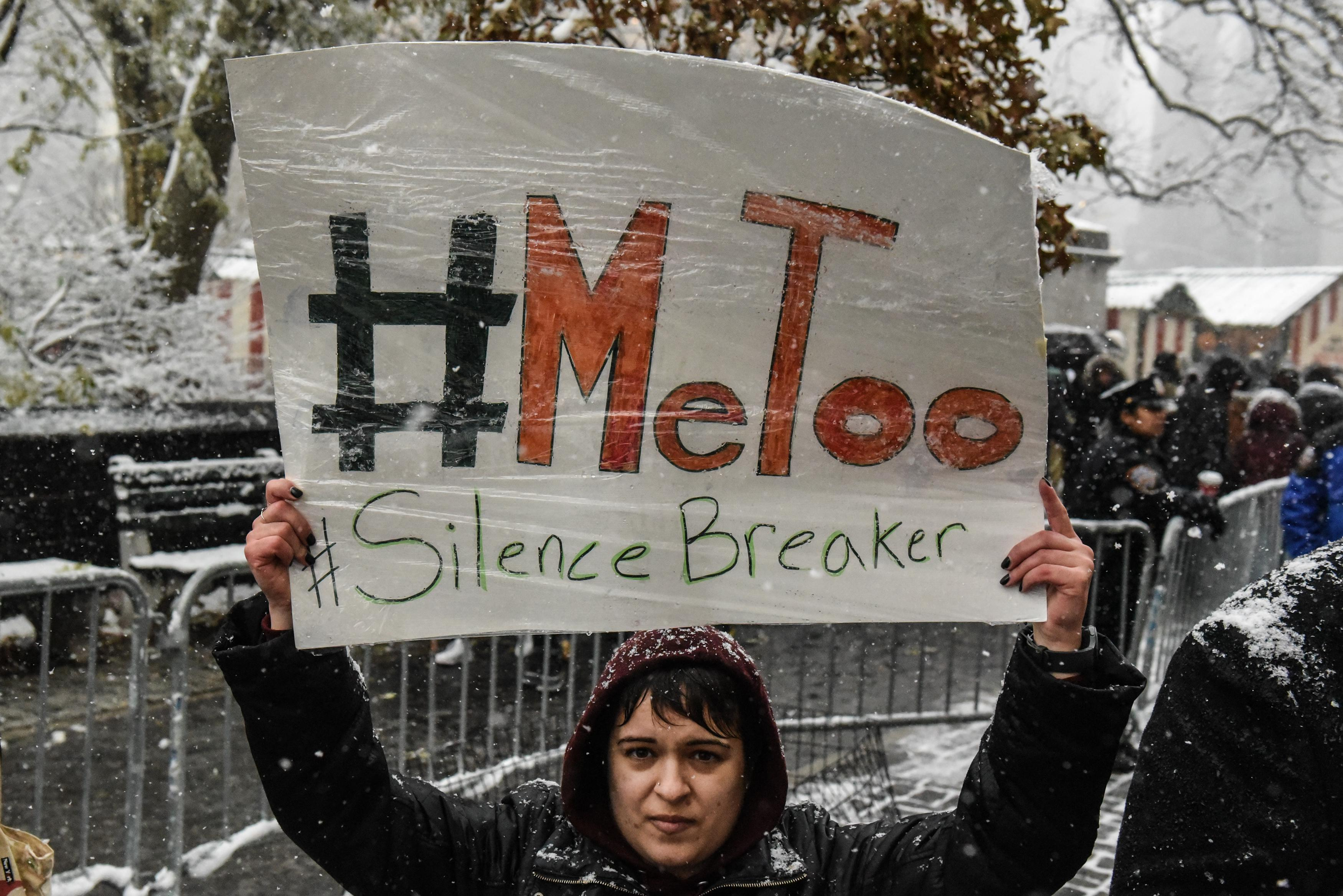 "A woman holds a sign that says, ""#MeToo #SilenceBreaker."""