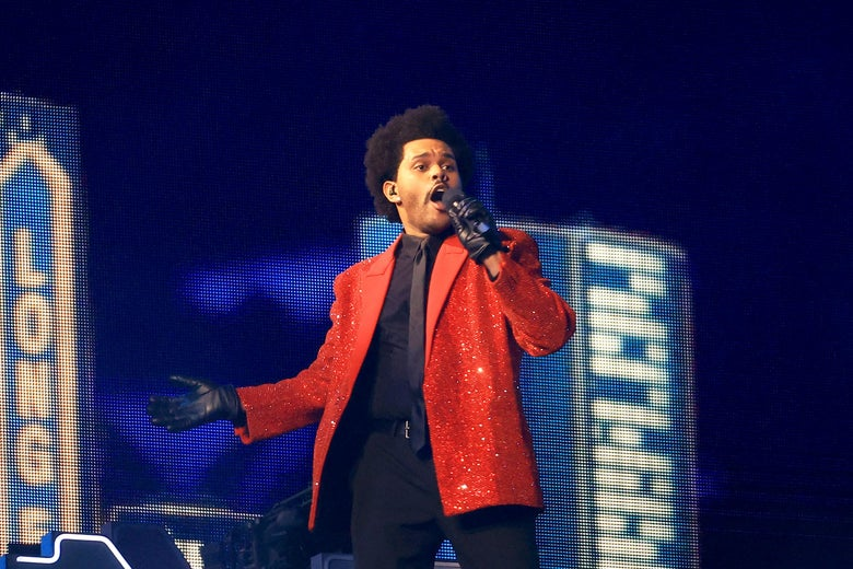 The Weeknd, in a red jacket and black suit, singing into a microphone at the Super Bowl.