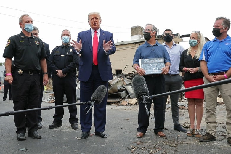 Trump gives a press conference with John Rode III and law enforcement officials standing beside him outside the destroyed shop.