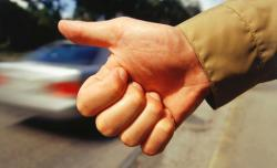 Man hitchhiking, Close-up of hand thumbing ride.