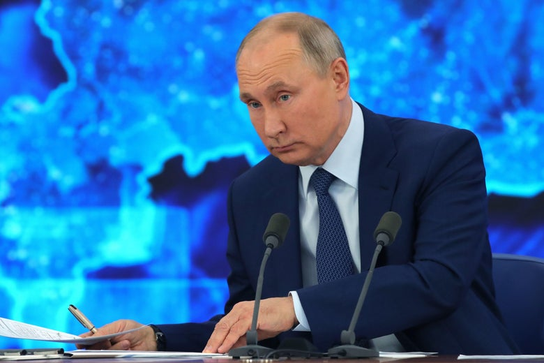 Putin at a desk, shuffling around papers.