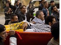 Mourners bury a fighter with aligned with Fatah's armed wing. Click image to expand.