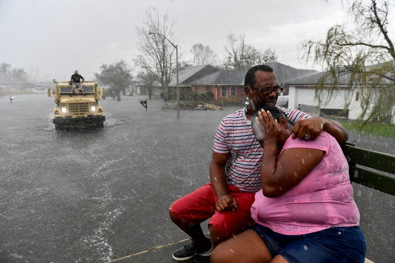 People react as a sudden rain shower soaks them with water while evacuating from their homes.