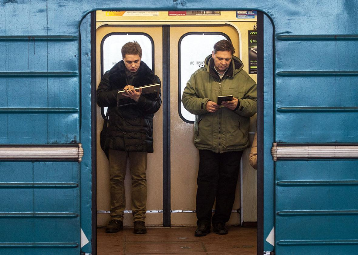 Commuters consult their electronic connected devices inside a train coach in the Moscow Metro, on December 1, 2014.