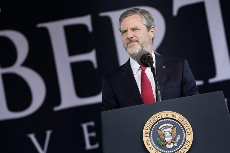 Falwell smiles, standing behind a podium bearing the U.S. presidential seal.
