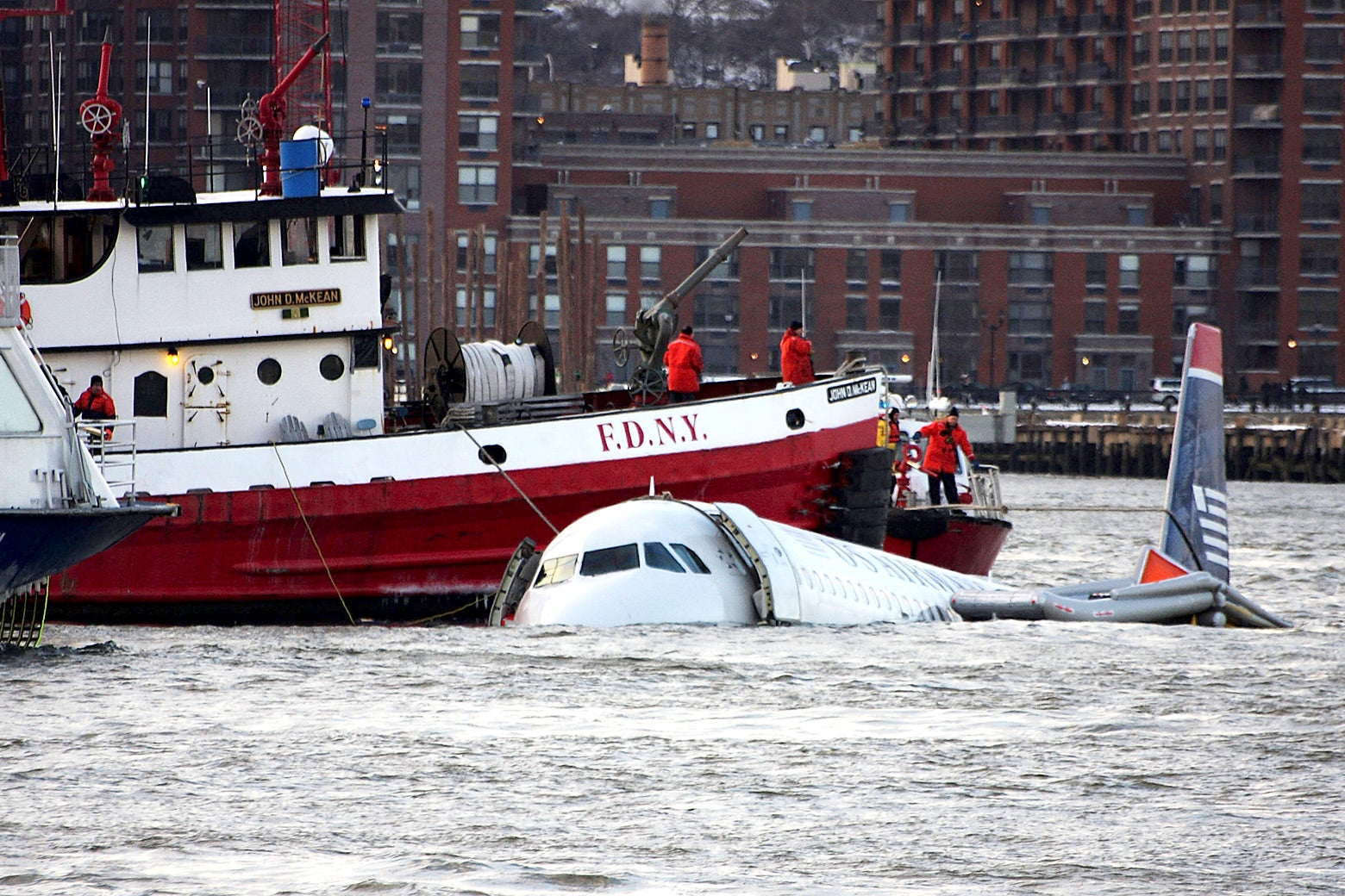 A New York City Fire Department boat floats next to partially submerged plane in the Hudson River.
