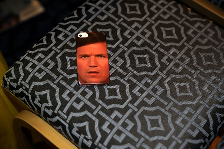 An iPhone whose case is covered by a photo of Tucker Carlson's face, resting on a conference room chair.