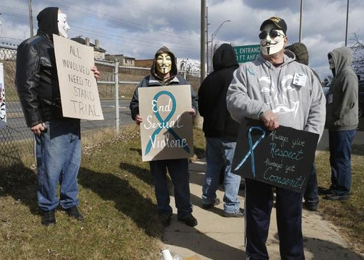 A group of protesters stand outside juvenile court in Steubenville, Ohio, March 14, 2013.
