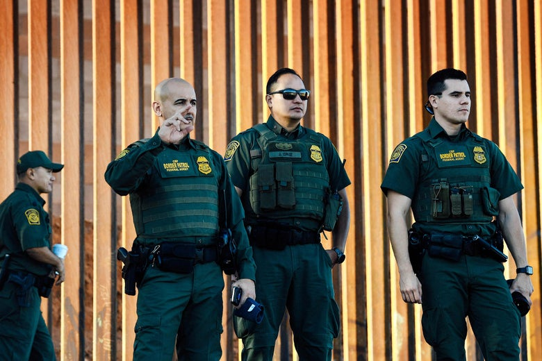 Border Patrol officers in front of a newly completed section of the U.S.-Mexico border wall.