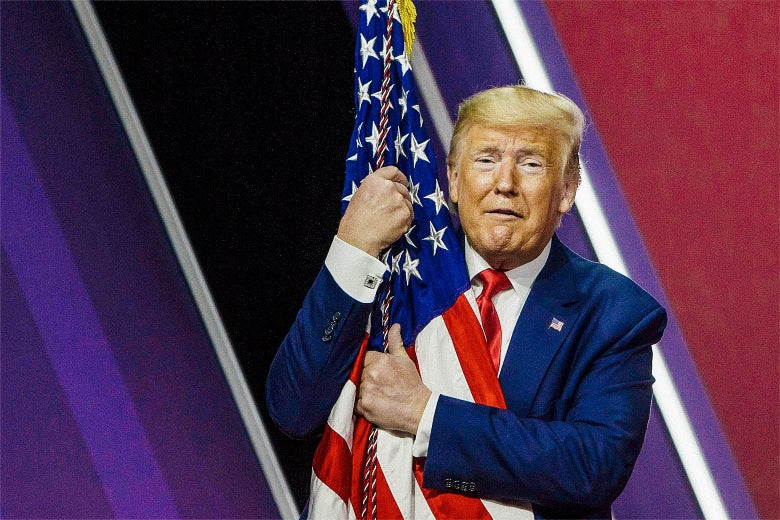 Trump makes a funny face while wrapping his arms around an American flag.