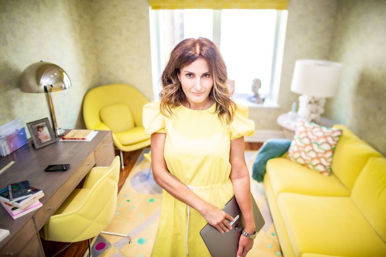 A woman in a yellow dress holds an Apple laptop while standing in a yellow room.