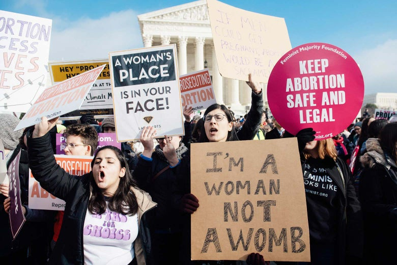 Pro-choice activists hold signs in response to anti-abortion activists participating in the March for Life outside the Supreme Court.