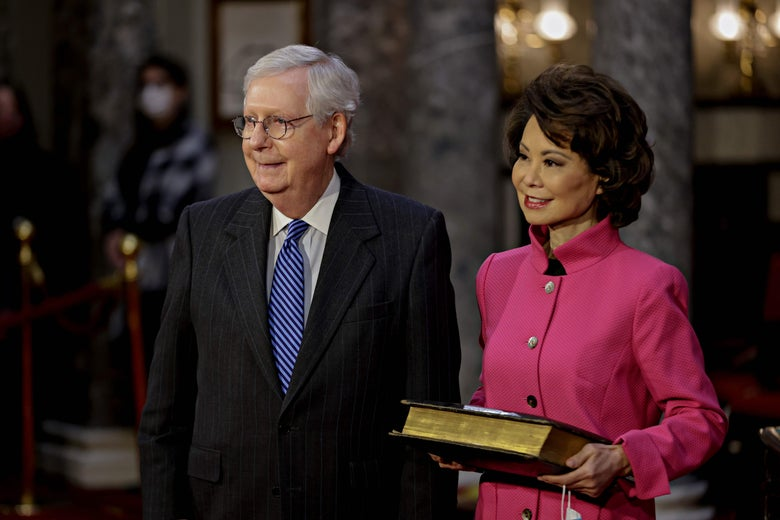 Chao holds a bible next to husband Mitch McConnell during a swearing-in ceremony at the U.S. Capitol.