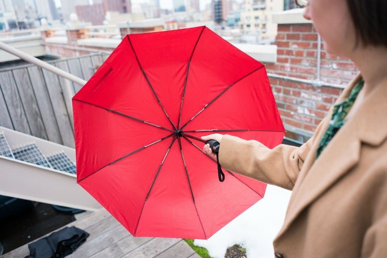 woman holding a red umbrella in front of her