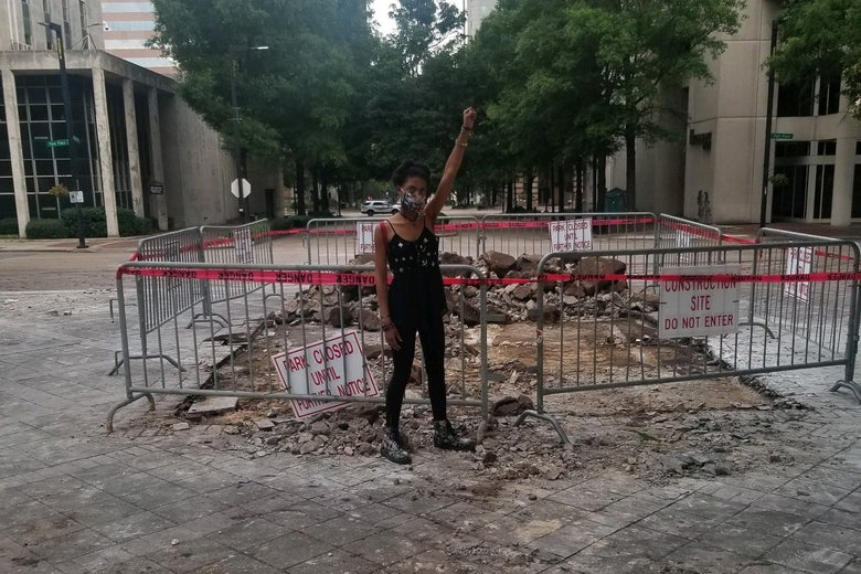 A young woman raises her fist in front of a torn-up patch of paved ground.
