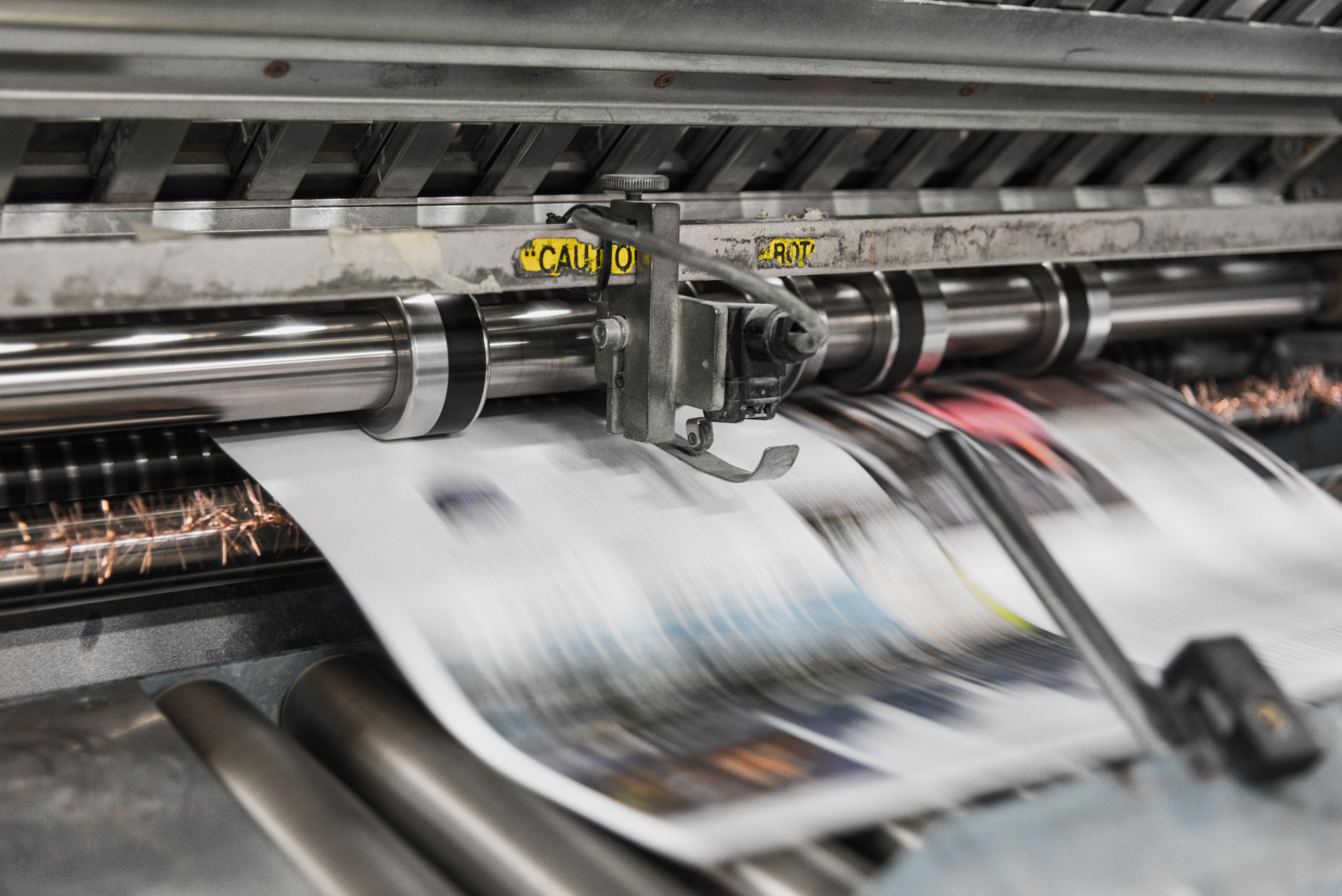 A newspaper coming out of a printing press.