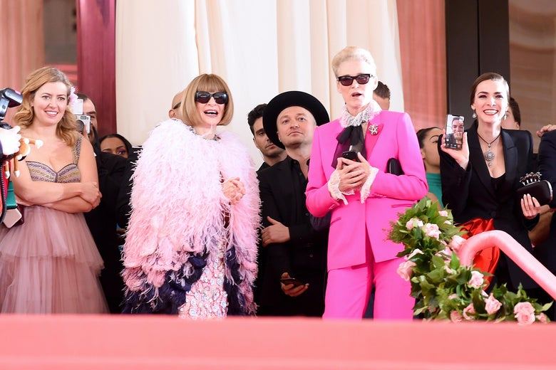 Anna Wintour, Lisa Love, and Bee Carrozzini stand at the top of the Met stairs. Shaffer holds a phone in her hand, screen facing out, showing the man she's FaceTiming.