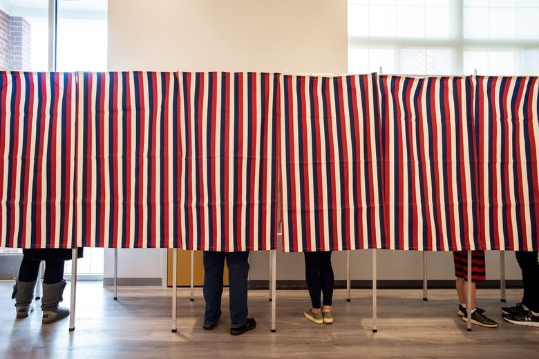 A red, white, and blue striped curtain hangs down over a row of six voting booths with five pairs of feet showing below them.