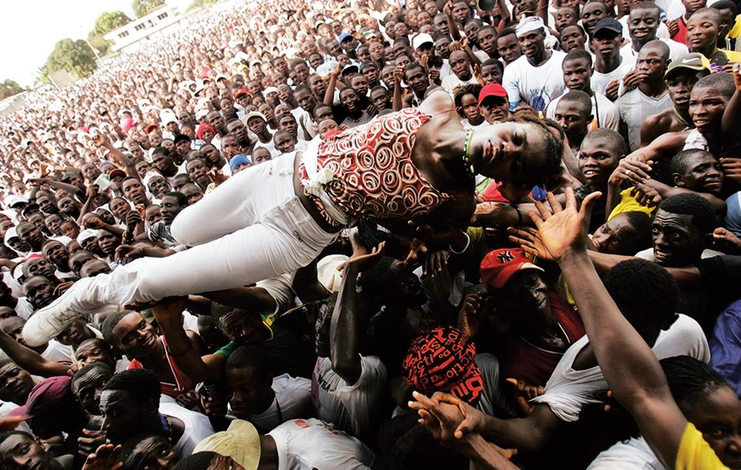 An unconscious woman is carried by supporters of Liberian presidential candidate George Weah after she fell ill from heat and lack of water on Oct. 8, 2005, in Monrovia, Liberia. The massive rally, held by former international soccer star Weah at his headquarters, attracted hundreds of thousands of supporters on a brutally hot day, with many collapsing from heat and thirst.