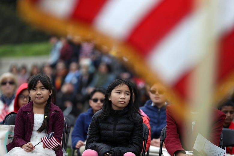 Children look on during a naturalization ceremony for kids between the ages of 6-12 at Crissy Field near the Golden Gate Bridge on August 17, 2018 in San Francisco, California.