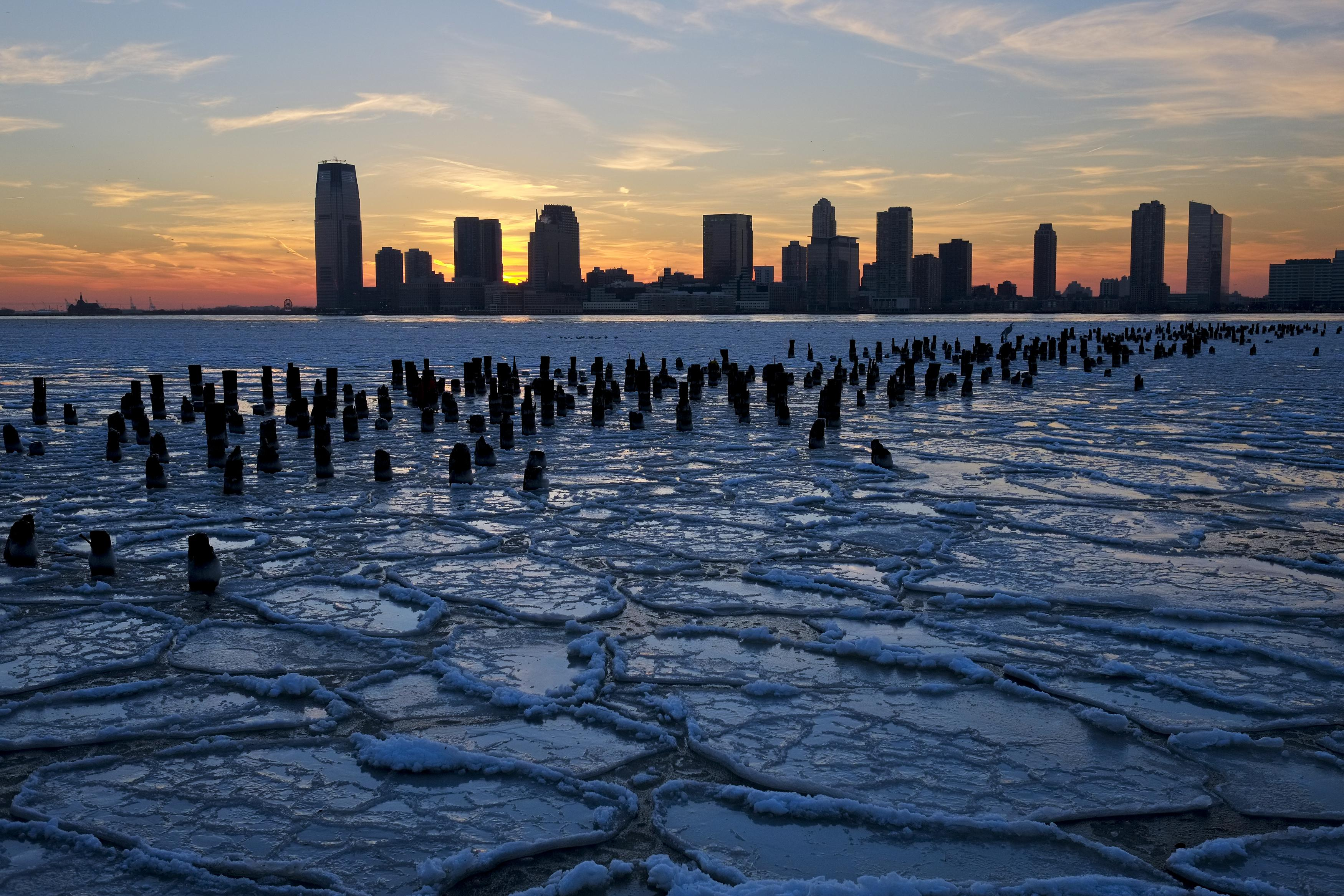 Ice floes fill the Hudson River as the New Jersey waterfront is seen during sunset in New York City.