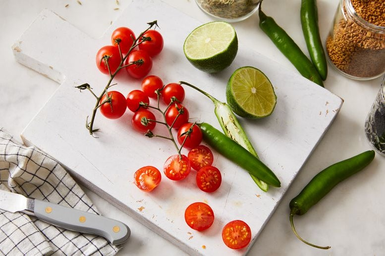 Cherry tomatoes, a halved lime, and green peppers on a cutting board with jars of spices next to them.