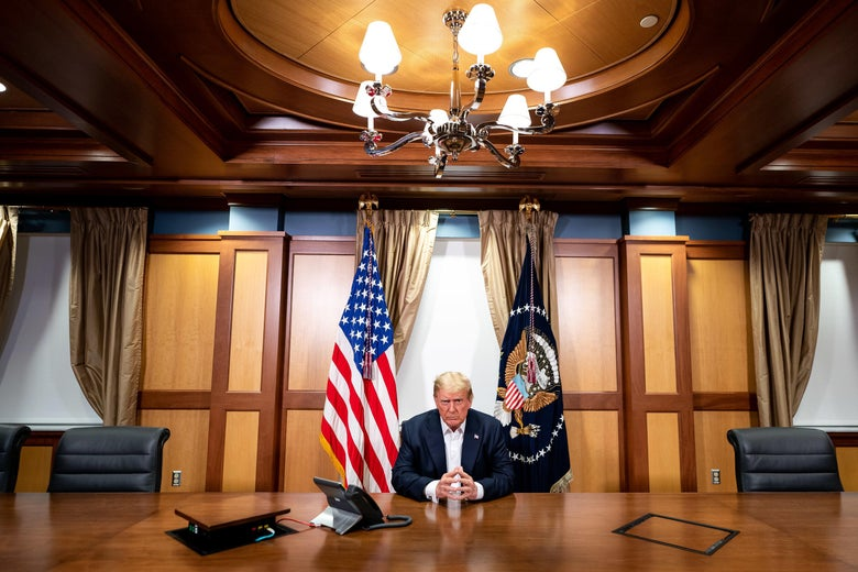 Trump sits at a conference room table, looking serious