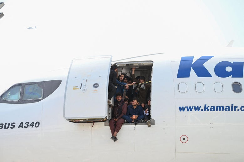Afghan people climb up on a plane and sit by the door as they wait at the Kabul airport.