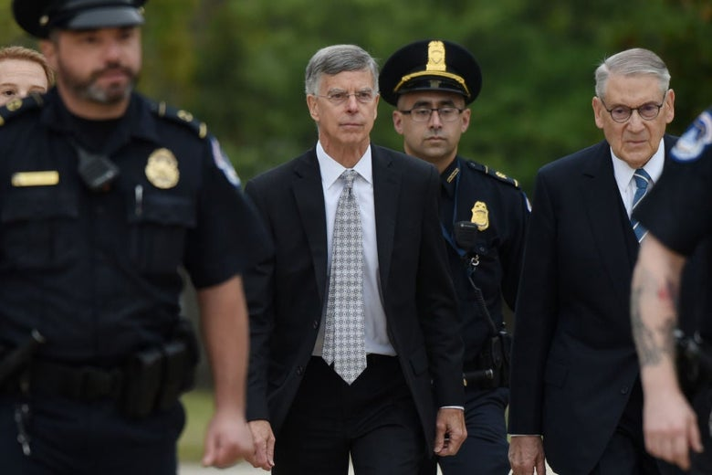 Taylor, wearing a black suit with a white shirt, walks outdoors while flanked by police officers.