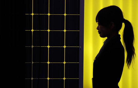 A woman is silhouetted next to a solar panel display by solar module supplier Upsolar at the International Photovoltaic Power Generation (PV) Expo in Tokyo, Japan.
