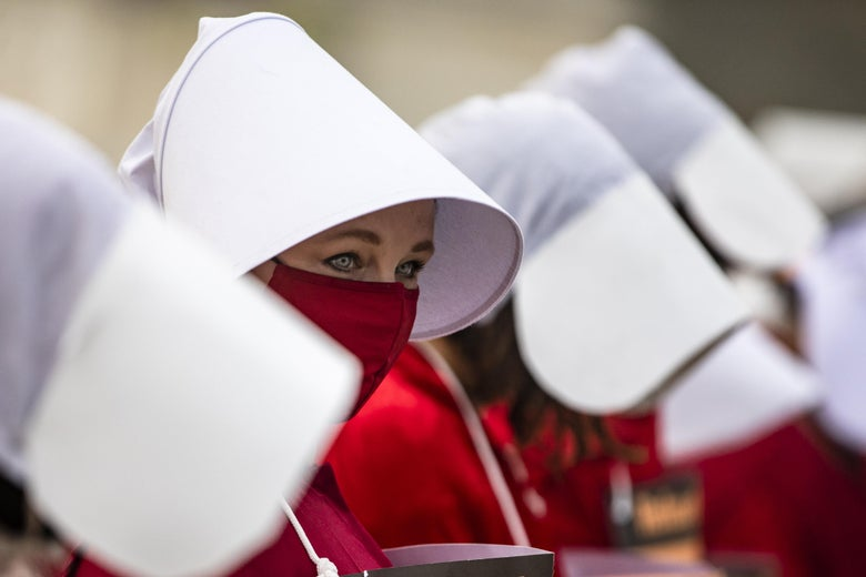 In a line of women wearing large white bonnets, one woman peeks over her red mask.