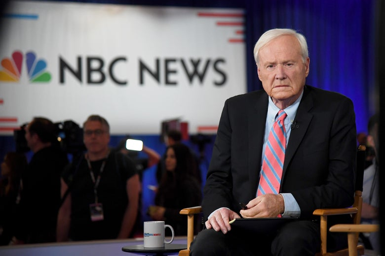 Chris Matthews seated, looking serious, before going on the air, with the NBC News logo on a screen in the background.