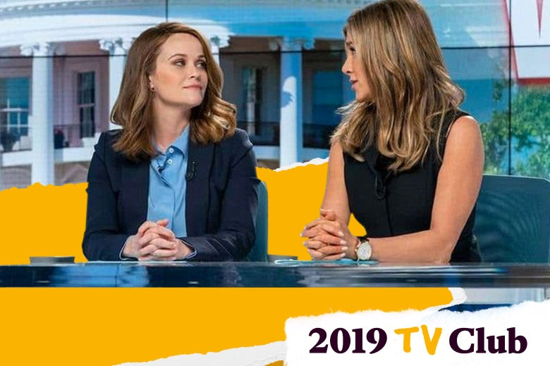 Reese Witherspoon and Jennifer Aniston look at each other mid-conversation at the morning TV show desk.