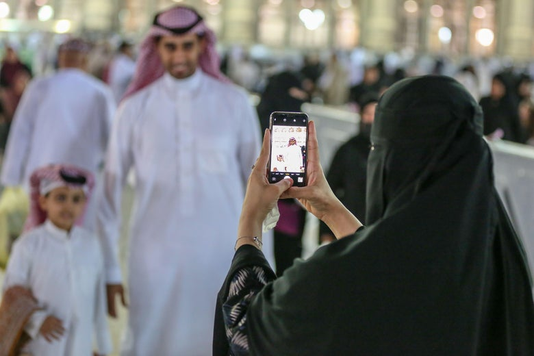 A woman takes a picture of her family after the Eid al-Fitr prayers at the Grand Mosque in the Saudi holy city of Mecca on June 4, 2019.