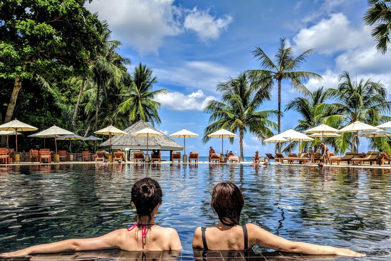 Two women in a pool with palm trees.