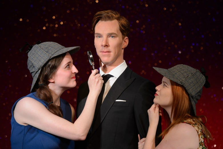 Fans Daisy England (L) and Charlie Mitchell (R) pose with Sherlock Holmes-style deerstalker hats and a magnifying glass around the new wax figure of British actor Benedict Cumberbatch as it is unveiled at Madame Tussauds in central London.