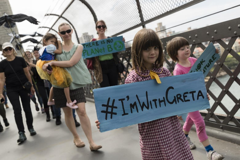 "A young girl on a bridge holds a sign saying ""#I'mWithGreta"""