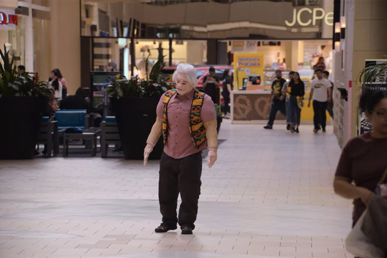 A man in an ill-fitting body suit in the middle of a mall.