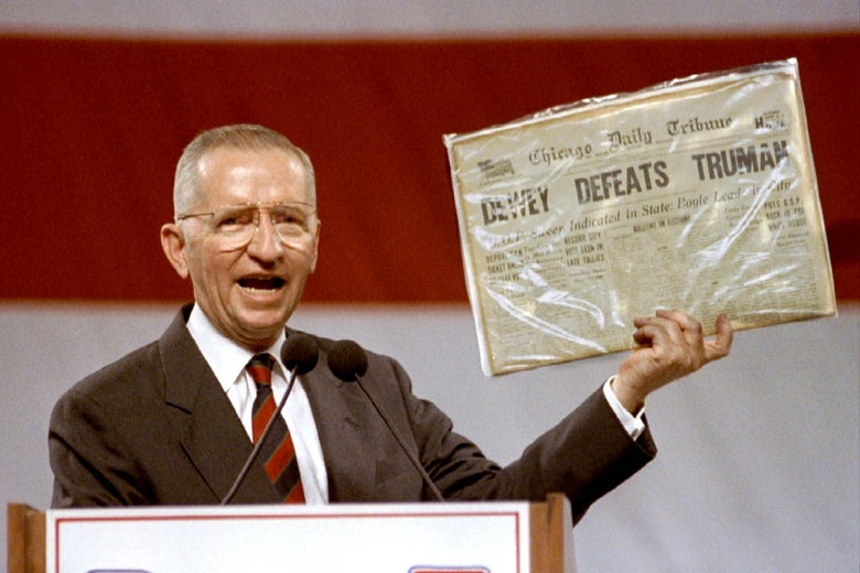 """Ross Perot holds up a copy of the Chicago Tribune with the famous """"Dewey Defeats Truman"""" headline."""