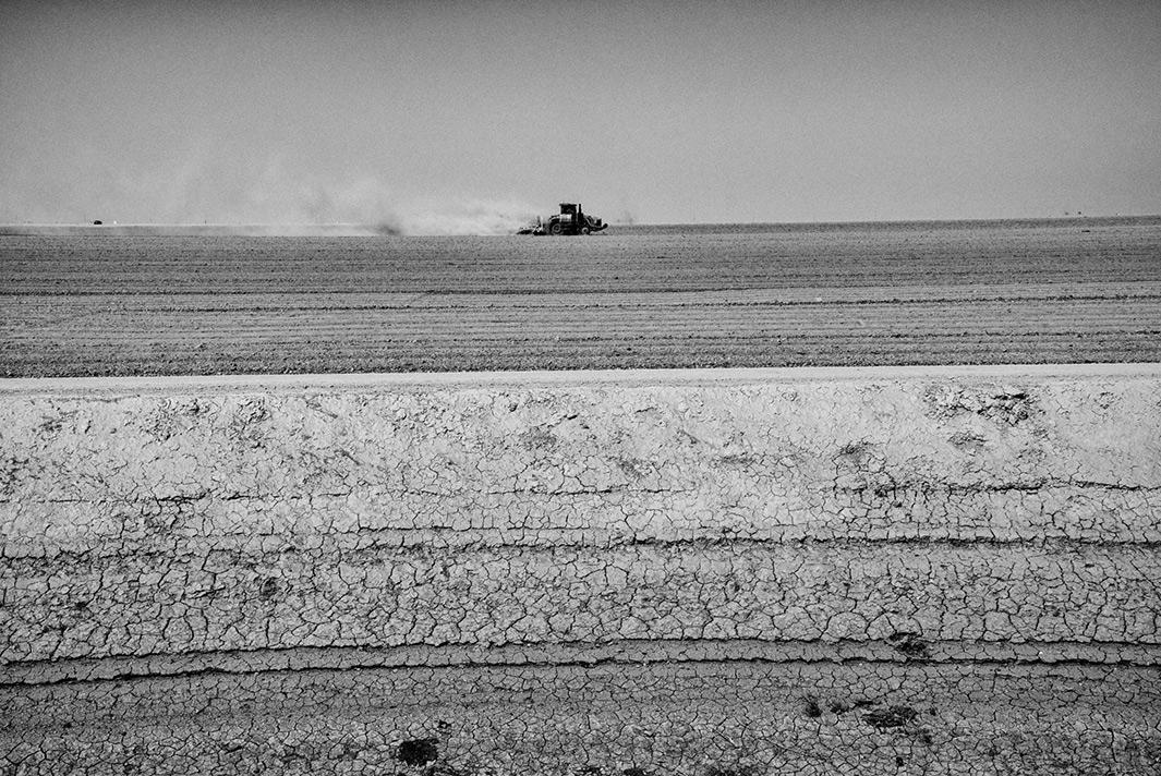 A tractor tills dry land near the Tulare Lake basin.