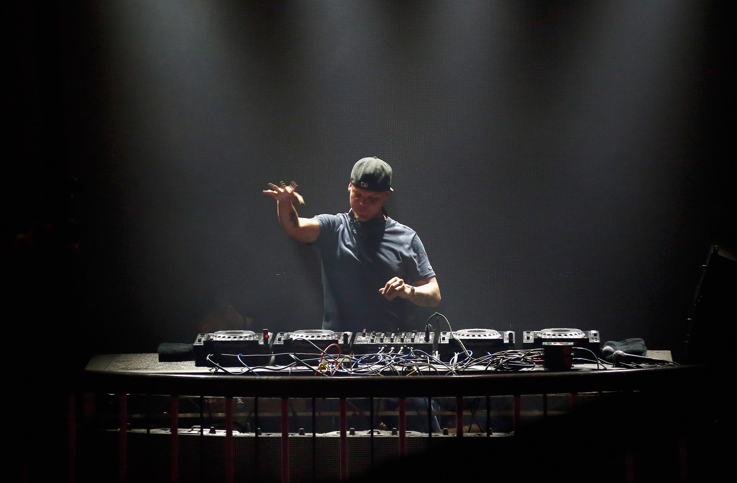 Avicii stands behind a turntable.