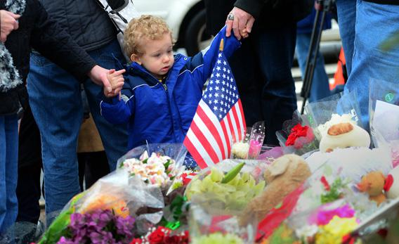 People pay their respects at a makeshift shrine to the victims of an elementary school shooting in Newtown, Connecticut, on Monday.