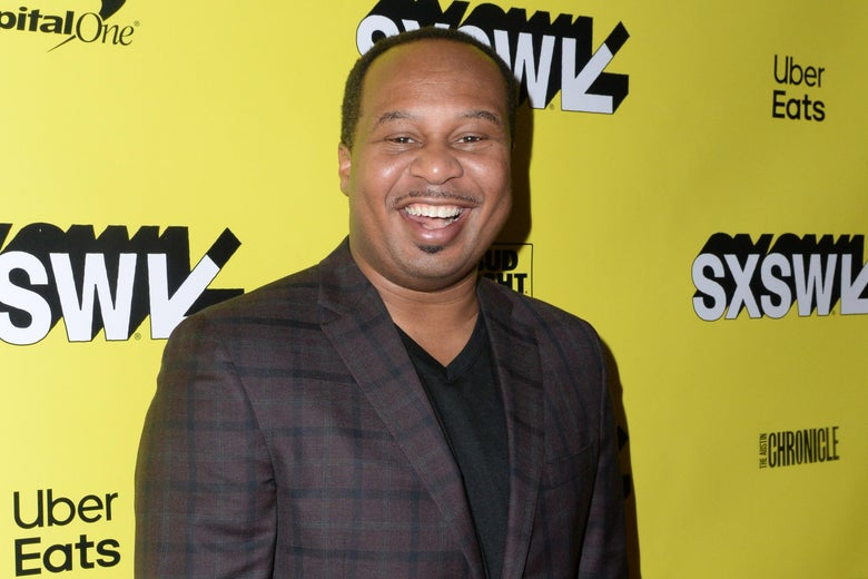 Roy Wood Jr. on a red carpet, smiling.