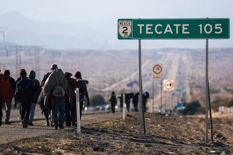 Migrants walk down a road beside a road sign that says Tecate 105.