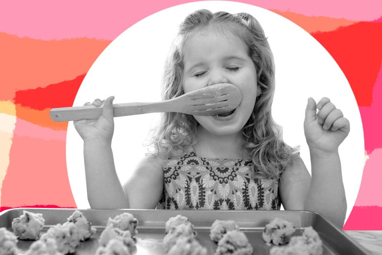 Young girl eating cookie dough off of a wooden spoon in front of a tray of cookies.